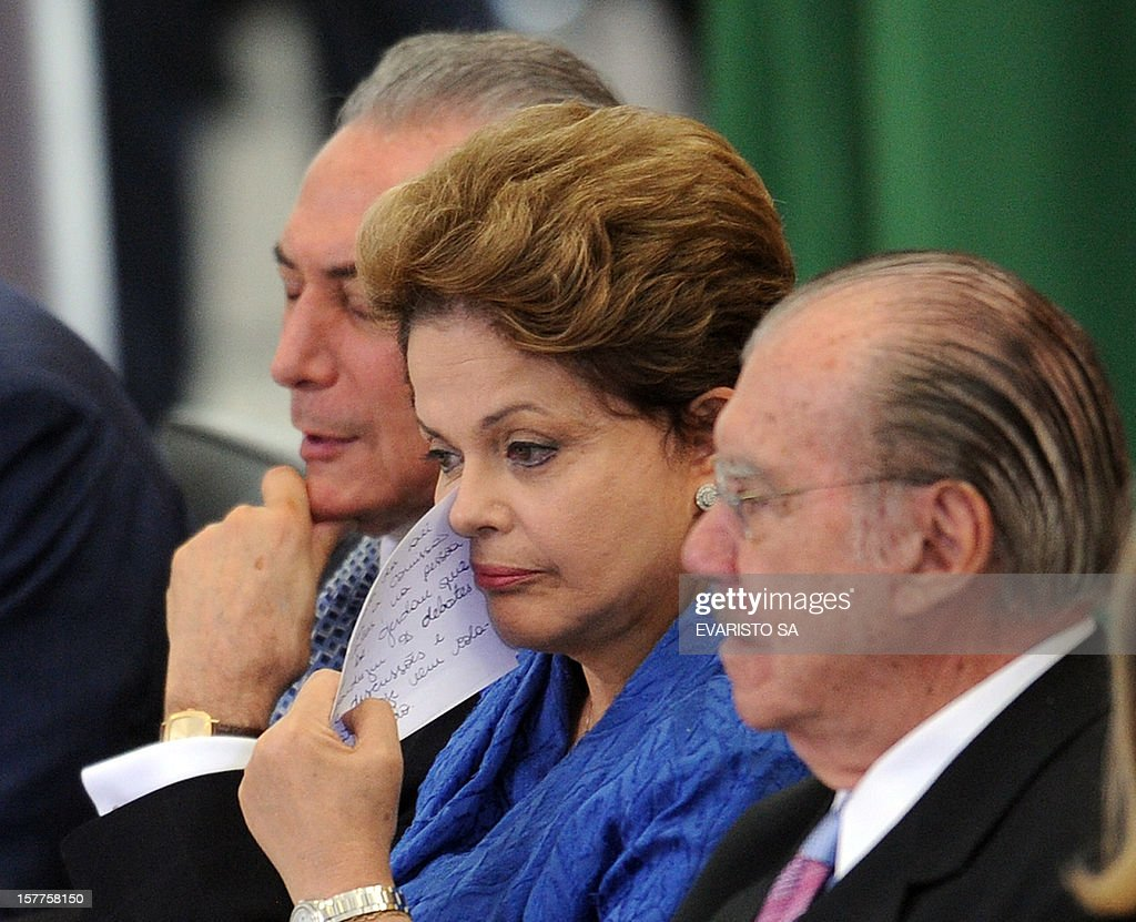 Brazilian President Dilma Rousseff (C) attends a ceremony to announce a program of investments in port logistics, sided by her Vice President Michel Temer (L) and Senate's President Jose Sarney (R), at Planalto Palace in Brasilia, on December 6, 2012. Brazilian architect Oscar Niemeyer, the Brazilian icon who revolutionized modern architecture and designed much of the country's futuristic capital Brasilia, died in Rio Wednesday at 104 and the President Rousseff said in a statement that 'It's a day to mourn his death. It's day to hail his life.' The architect's body is to be flown to Brasilia today for a funeral wake at the presidential palace, one of his major works. AFP PHOTO/Evaristo SA