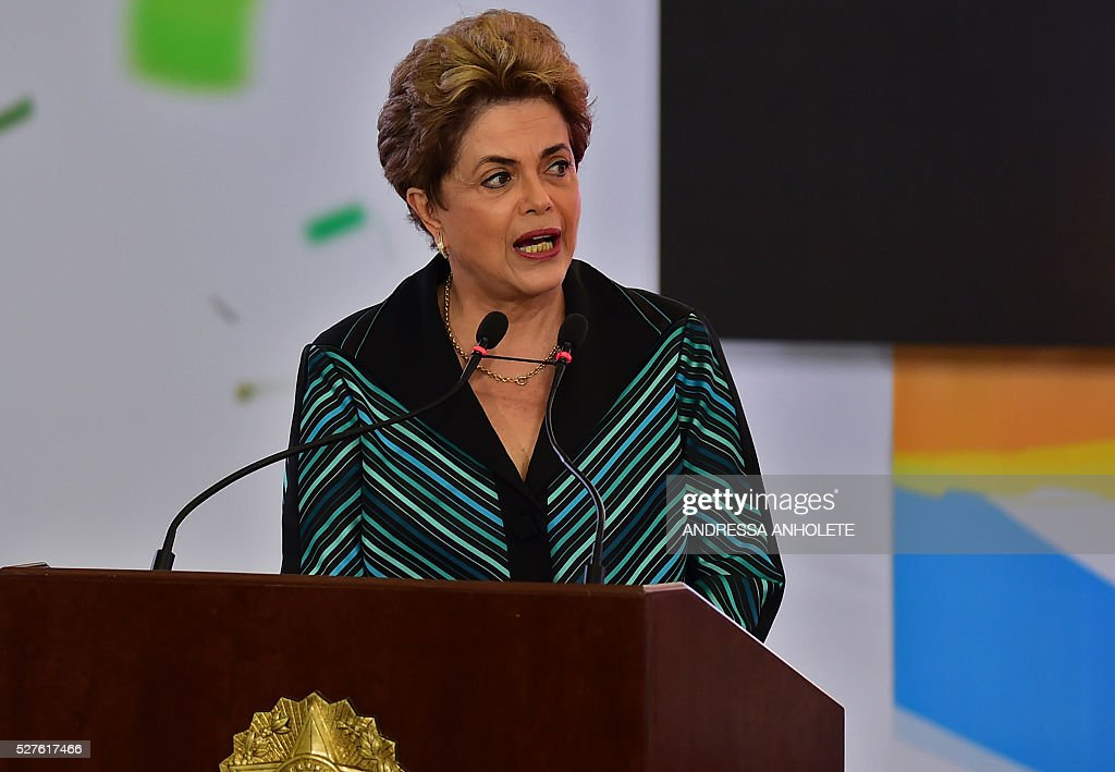Brazilian President Dilma Rousseff delivers a speech during the ceremony to receive the Olympic Flame at Planalto Palace in Brasilia following it's arrival in Brazil on May 3, 2016 ahead of the Rio 2016 Olympic Games in August. The Olympic flame arrived in Brasilia May 3 aboard a flight from Geneva to embark on a procession across Brazil culminating in the opening ceremony of the 2016 Games in Rio de Janeiro. The torch will travel to more than 300 towns and cities carried by some 12,000 relay runners before arriving August 5 at the mythic Maracana stadium to kick off the first Olympics in South America. / AFP / ANDRESSA