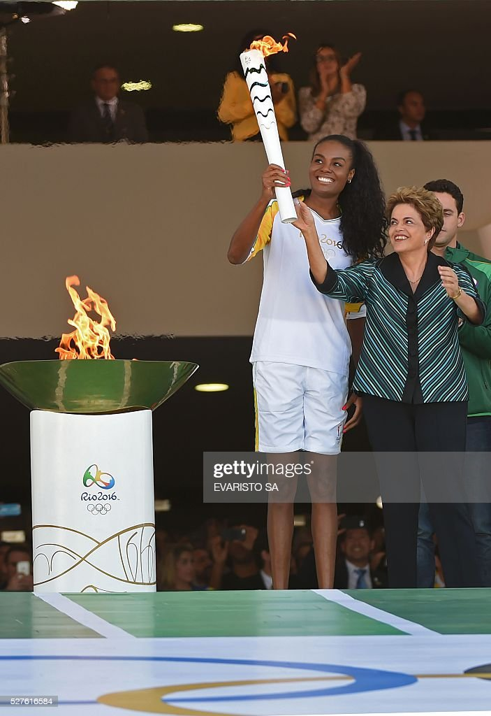 Brazilian President Dilma Rousseff (R) hands the Olympic torch to Brazilian volleyball player Fabiana Claudino at Planalto Palace in Brasilia following the flame's arrival in Brazil on May 3, 2016, to begin its journey across the country before the start of the 2016 Olympic Games on August 5. The Olympic flame arrived in Brasilia May 3 aboard a flight from Geneva to embark on a procession across Brazil culminating in the opening ceremony of the 2016 Games in Rio de Janeiro. The torch will travel to more than 300 towns and cities carried by some 12,000 relay runners before arriving August 5 at the mythic Maracana stadium to kick off the first Olympics in South America. / AFP / EVARISTO SA