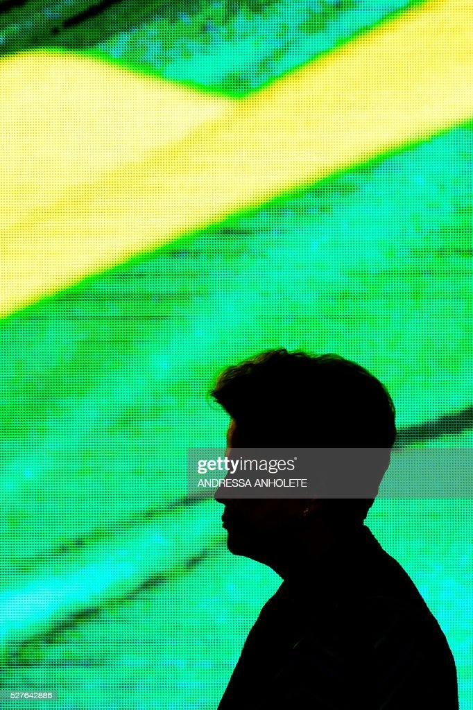 Brazilian President Dilma Rousseff is sillohuetted against a screen during the ceremony to receive the Olympic Flame at Planalto Palace in Brasilia following it's arrival in Brazil on May 3, 2016 ahead of the Rio 2016 Olympic Games in August. The Olympic flame arrived in Brasilia May 3 aboard a flight from Geneva to embark on a procession across Brazil culminating in the opening ceremony of the 2016 Games in Rio de Janeiro. The torch will travel to more than 300 towns and cities carried by some 12,000 relay runners before arriving August 5 at the mythic Maracana stadium to kick off the first Olympics in South America. / AFP / ANDRESSA