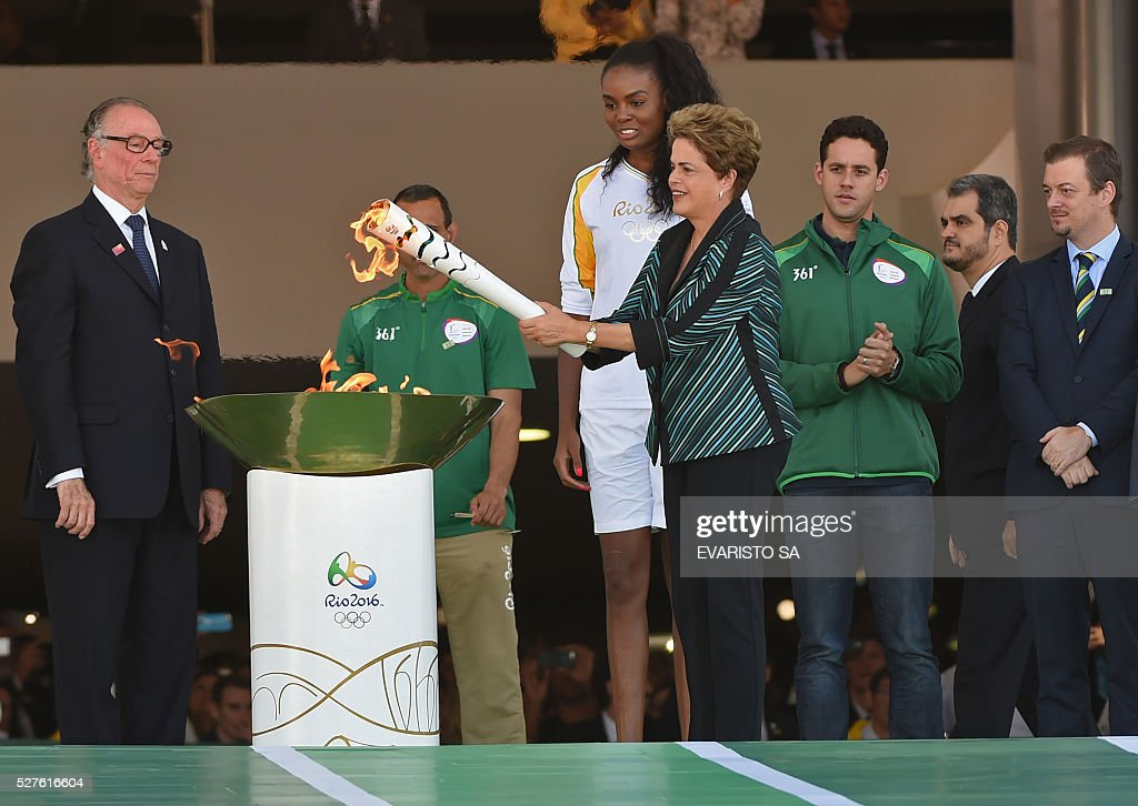 Brazilian President Dilma Rousseff lights the Olympic torch at Planalto Palace in Brasilia following the flame's arrival from Geneva on May 3, 2016, beginning the flame's journey across the country before the start of the 2016 Olympic Games on August 5. The Olympic flame arrived in Brasilia May 3 aboard a flight from Geneva to embark on a procession across Brazil culminating in the opening ceremony of the 2016 Games in Rio de Janeiro. The torch will travel to more than 300 towns and cities carried by some 12,000 relay runners before arriving August 5 at the mythic Maracana stadium to kick off the first Olympics in South America. / AFP / EVARISTO SA