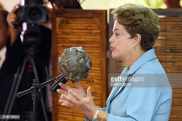 Brazilian President Dilma Rousseff plays with a ball made of palm leaves as she delivers a speech during the launch of the I World Games of the...