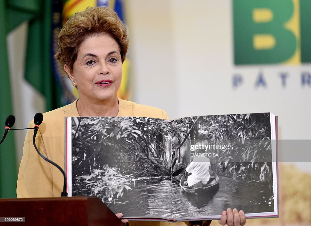 Brazilian President Dilma Rousseff shows a photobook from Brazilian photographer Araquem Almeida during a ceremony to announce the extension of the stay of Brazilian doctors trained abroad and foreigners participating in the More Medical Program, at Planalto Palace in Brasilia, on April 29, 2016. The Brazilian Senata formed a committee that will consider whether to impeach President Dilma Rousseff, who has accused her opponents of mounting a constitutional coup. / AFP / EVARISTO SA