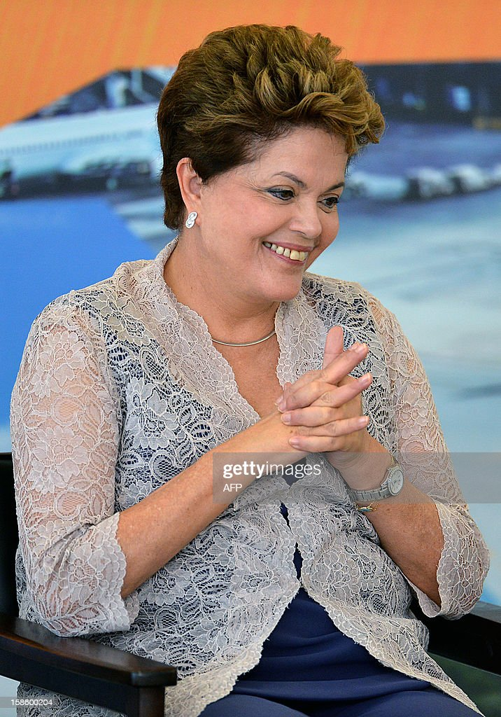 Brazilian President Dilma Rousseff smiles during a ceremony to announce investments in airports in Brazil, at Planalto Palace, in Brasilia, on December 20, 2012. Brazilian government plans a 18 billion Reales (about 9 billion dollars) investment in Brazilian airports --including those in small towns-- to face necessary logistics for the upcoming 2014 FIFA World Cup and the 2016 Olympic Games. AFP PHOTO/Pedro LADEIRA