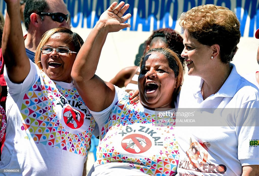 Brazilian President Dilma Rousseff (R) takes part in an awareness campaign during the day of national mobilization against the Aedes aegypti mosquito --that transmits dengue, chikungunya fever and zika virus-- in the neighbourhood of Santa Cruz 60km in Rio de Janeiro, Brazil, on February 13, 2016. Some 220,000 members of the armed forces have been deployed to visit 3 million homes throughout Brazil during the day. AFP PHOTO/VANDERLEI ALMEIDA / AFP / VANDERLEI ALMEIDA