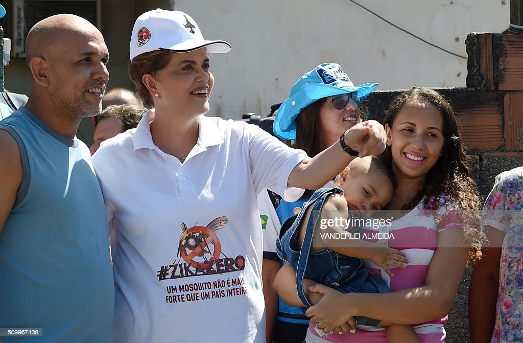 Brazilian President Dilma Rousseff (C) takes part in an awareness campaign during the day of national mobilization against the Aedes aegypti mosquito --that transmits dengue, chikungunya fever and zika virus-- in the neighbourhood of Santa Cruz 60km in Rio de Janeiro, Brazil, on February 13, 2016. Some 220,000 members of the armed forces have been deployed to visit 3 million homes throughout Brazil during the day. AFP PHOTO/VANDERLEI ALMEIDA / AFP / VANDERLEI ALMEIDA