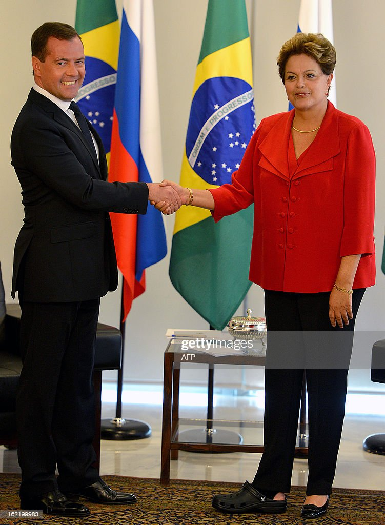 Brazilian President Dilma Rousseff (R) -- wearing different shoes after breaking her right big toe in a domestic accident during carnival -- shakes hands with Russia's Prime Minister Dmitry Medvedev at Planalto Palace in Brasilia, on February 20, 2013. Medvedev is on a three-day visit to Brazil on the sidelines of an annual bilateral cooperation meeting. AFP PHOTO/Pedro LADEIRA