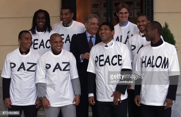 Brazilian President Fernando Henrique Cardoso jokes 26 October 2001 at the Brazilian embassy in Madrid with a group of Brazilian soccer players...