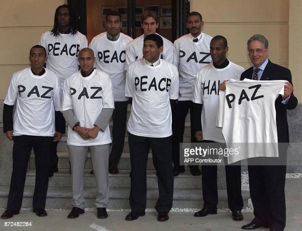 Brazilian President Fernando Henrique Cardoso receives in the Brazilian embassy in Madrid 26 October 2001 a group of Brazilian soccer players wearing...