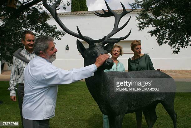 Brazilian President Luiz Inacio Lula da Silva strokes a statue of a deer under the eye of Spanish Prime Minister Jose luis Rodriguez Zapatero his...