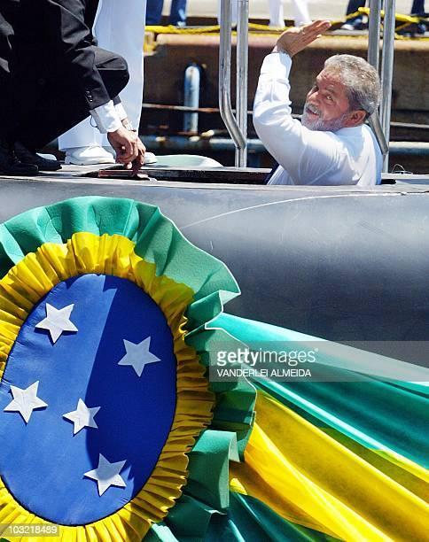Brazilian President Luiz Inacio Lula da Silva waves as he gets into the new Brazilian Tupi war submarine named 'S34 Tikuna' in honor of an Amazonic...