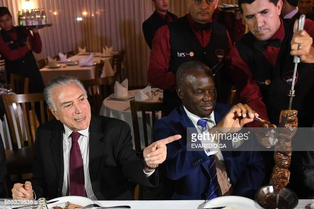Brazilian President Michel Temer and Angola's ambassador Nelson Manuel Cosme eat barbecue in a steak house in Brasilia after a meeting with...