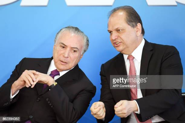 Brazilian President Michel Temer and Health Minister Ricardo Barros talk during the ceremony to grant the Order of Medical Merit an order conferred...