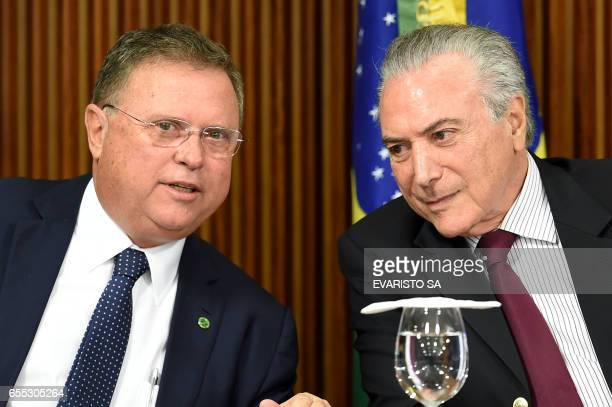 Brazilian President Michel Temer and his Agriculture Minister Blairo Maggi talk during a meeting with ambassadors from countries that import...