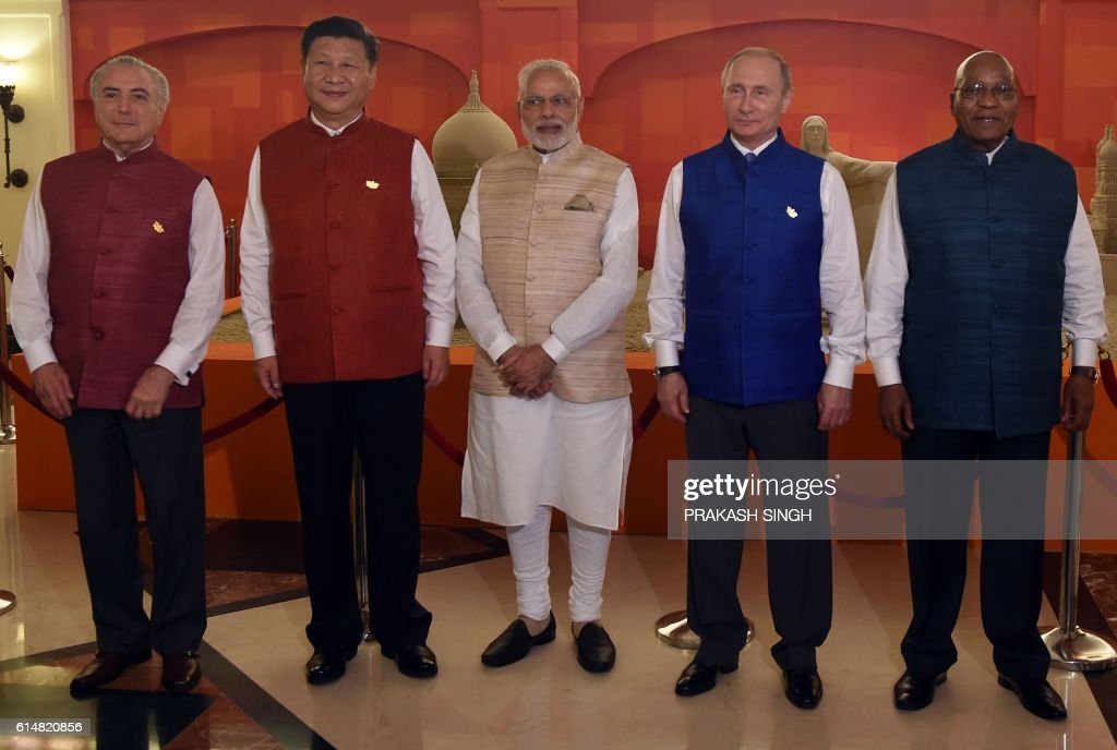 TOPSHOT - Brazilian President Michel Temer (L), Chinese President Xi Jinping (2L), Indian Prime Minister Narendra Modi (C), Russian President Vladimir Putin (2R) and South Africa President Jacob Zuma pose in front of sand art representing national monuments from BRICS member countries ahead of an informal dinner during the BRICS summit in Goa on October 15, 2016. India is hosting the BRICS Summit in the southern state of Goa on October 15-16, 2016. / AFP / PRAKASH