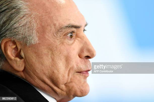 Brazilian President Michel Temer gestures as he delivers a speech during the ceremony to grant the Order of Medical Merit an order conferred by the...