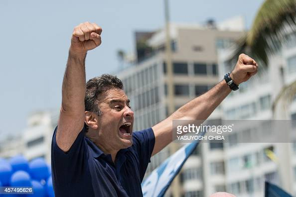 Brazilian presidential candidate for the Brazilian Social Democracy Party Aecio Neves gestures at supporters during his campaign at Copacabana beach...