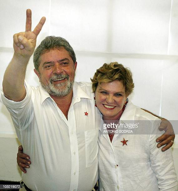 Brazilian presidential candidate Luiz Inacio Lula da Silva of the Worker's Party with his wife Marisa makes the 'V' sign 27 October 2002 shortly...