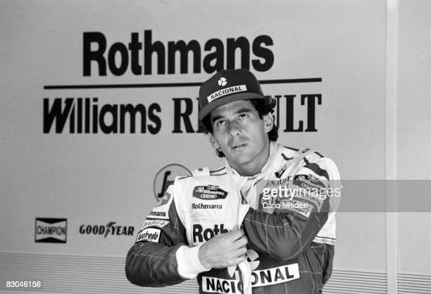Brazilian race car driver Ayrton Senna reaches into his jumpsuit to scratch while watching a qualification session for the San Marino Formula 1 Grand...