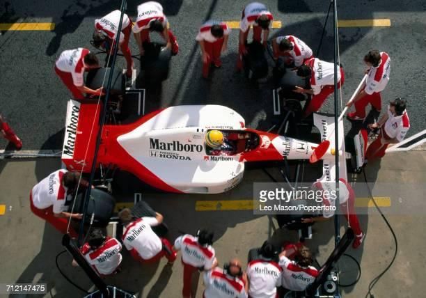 Brazilian racing driver Ayrton Senna driving a Honda Marlboro McLaren McLaren MP4/6 Honda RA121E 35 V12 racing car is surrounded by his pit crew...