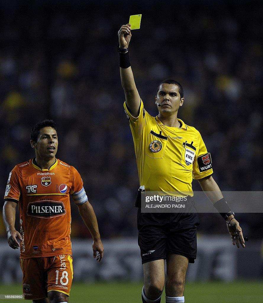 Brazilian referee Ricardo Marques shows a yellow card during their Copa Libertadores 2013 Group 1 football match between Argentina's Boca Juniors and Ecuador's Barcelona, at 'La Bombonera' stadium in Buenos Aires, Argentina, on April 3, 2013.