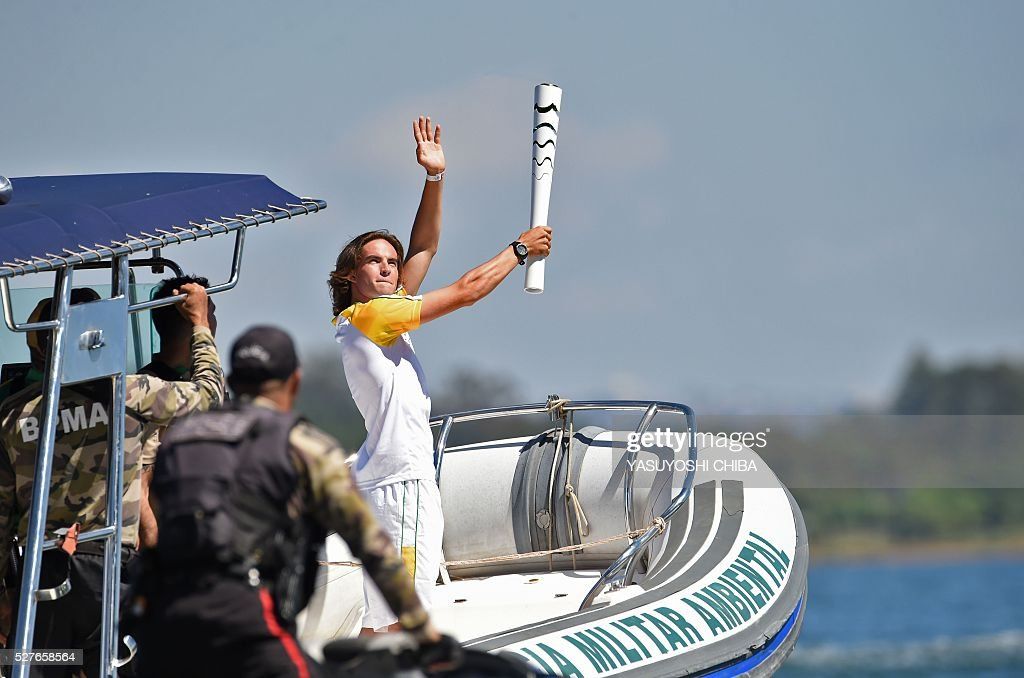 Brazilian sailor Felipe Rondina carries the Olympic flame on a speedboat at Lake Paranoa in Brasilia on May 3, 2016. Embattled President Dilma Rousseff greeted the Olympic flame in Brazil on Tuesday, promising not to allow a raging political crisis, which could see her suspended within days, to spoil the Rio Games. The torch will now be carried in a relay by 12,000 people through 329 cities, ending in Rio's Maracana stadium on August 5 for the opening ceremony. / AFP / YASUYOSHI