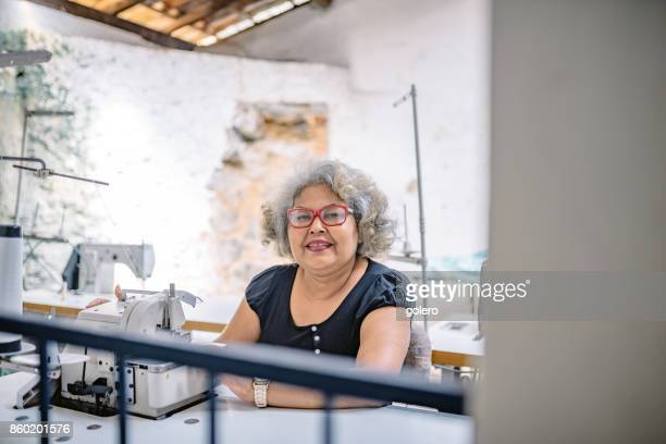 brazilian senior woman at sewing machine in tailor work room of social project