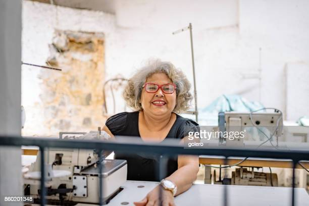 senior Brasilianerin an Nähmaschine im Arbeitsraum Schneider