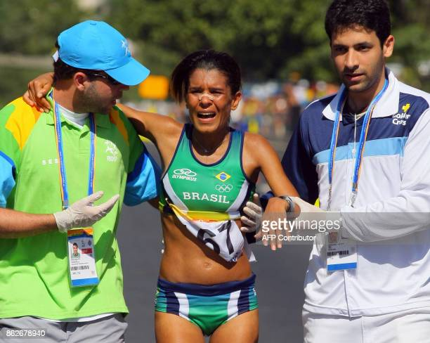 Brazilian Sirlene Pinho is helped by assitants after crossing the women marathon finish line in third place on July 22nd during the XV Pan American...
