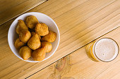 """Brazilian snack """"coxinha"""" and beer on wood table"""