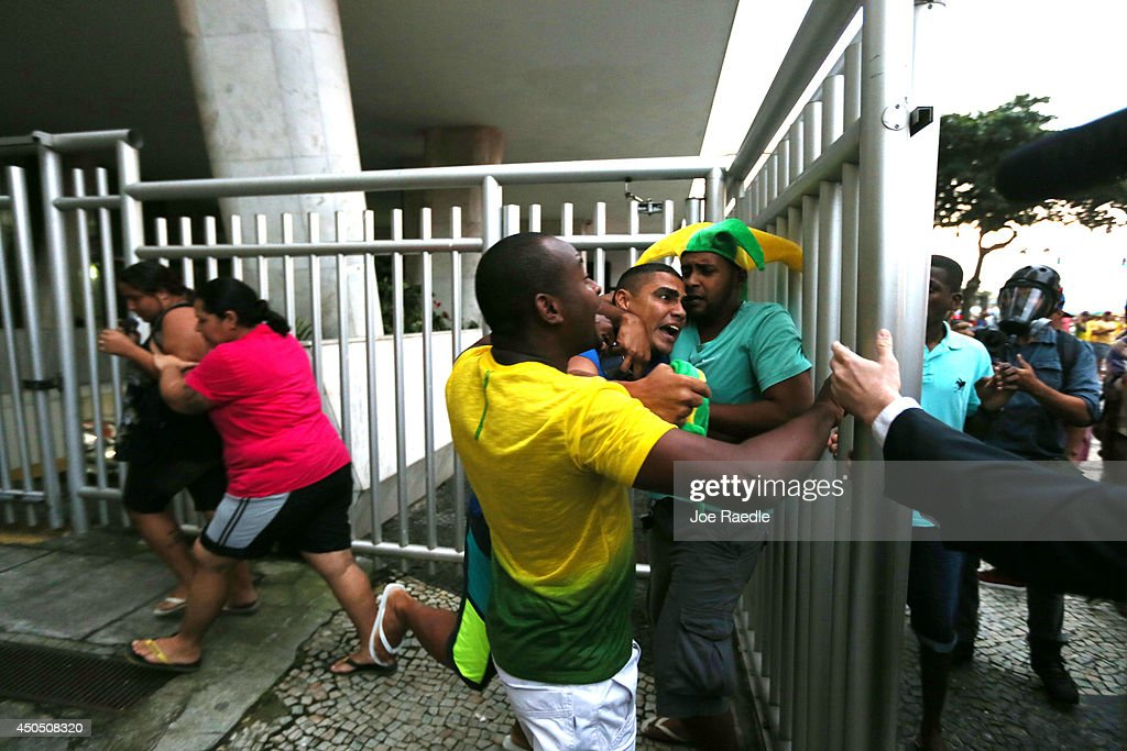A Brazilian soccer fan is restrained from fighting anti-World Cup protestors that were marching by June 12, 2014 in Rio de Janeiro, Brazil. This is the first day of World Cup play.