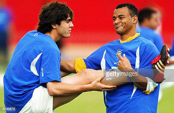 Brazilian soccer team captain Cafu helps to stretch his teammate Kaka 18 November 2003 during a practice at the Pinheirao stadium in Curitiba Brazil...