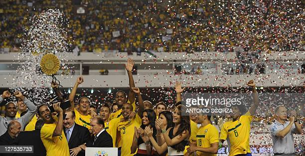 Brazilian soccer team captain Ronaldinho Gaucho holds the trophy as teammates celebrate their title of Americas Super Classic chapionship after...