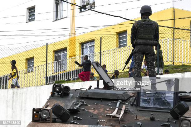 A Brazilian soldier in combat gear standing atop an armoured personnel carrier positioned on a street keeps watch during a predawn antigang operation...