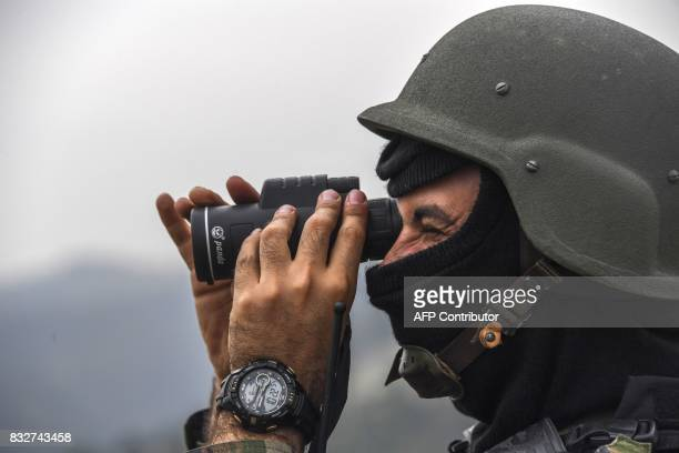 A Brazilian soldier scans with a scope lower terrain from the top of a hill during a predawn antigang operation in Niteroi greater Rio de Janeiro...