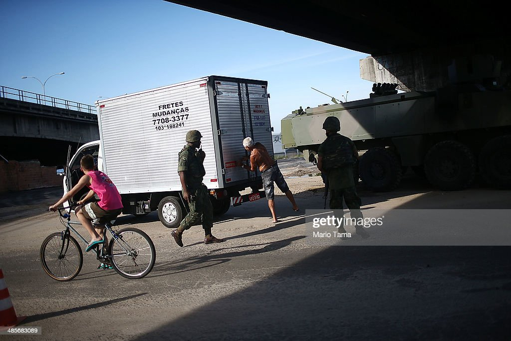 Brazilian soldiers inspect a man's truck in the occupied Complexo da Mare, one of the largest 'favela' complexes in Rio, on April 19, 2014 in Rio de Janeiro, Brazil. The Brazilian government has deployed nearly 3,000 federal troops to occupy the group of violence-plagued slums ahead of the June 12 start of the 2014 FIFA World Cup. The group of 16 communities house around 130,000 residents and had been dominated by drug gangs and militias. Mare is located close to Rio's international airport and has been mentioned as a likely pacification target for the police amid the city's efforts to improve security ahead of the 2014 FIFA World Cup and Rio 2016 Olympic Games.