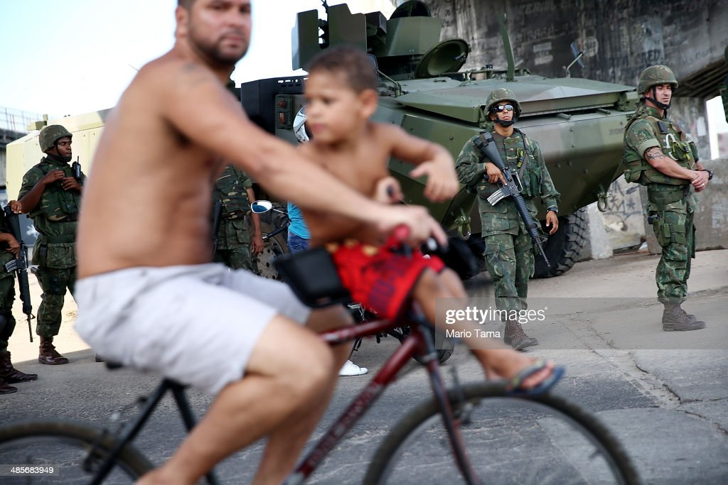 Brazilian soldiers keep watch as a man and boy bike past in the occupied Complexo da Mare, one of the largest 'favela' complexes in Rio, on April 19, 2014 in Rio de Janeiro, Brazil. The Brazilian government has deployed nearly 3,000 federal troops to occupy the group of violence-plagued slums ahead of the June 12 start of the 2014 FIFA World Cup. The group of 16 communities house around 130,000 residents and had been dominated by drug gangs and militias. Mare is located close to Rio's international airport and has been mentioned as a likely pacification target for the police amid the city's efforts to improve security ahead of the 2014 FIFA World Cup and Rio 2016 Olympic Games.