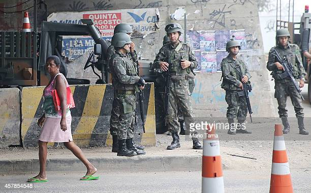 Brazilian soldiers keep watch at a checkpoint in the Complexo da Mare 'favela' or community on the day before runoff elections on October 25 2014 in...