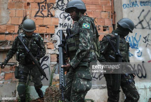 Brazilian soldiers walk during a 'Mega Operation' conducted by the Brazilian Armed Forces along with police against gang members in seven of Rio's...