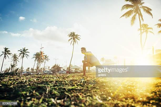 brazilian sportsman stretching at tropic coast at sunset