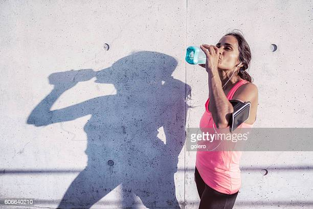 brazilian sportswoman drinking in front of concrete facade after running