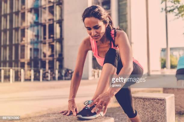 brazilian sportswoman tying shoe in berlin city