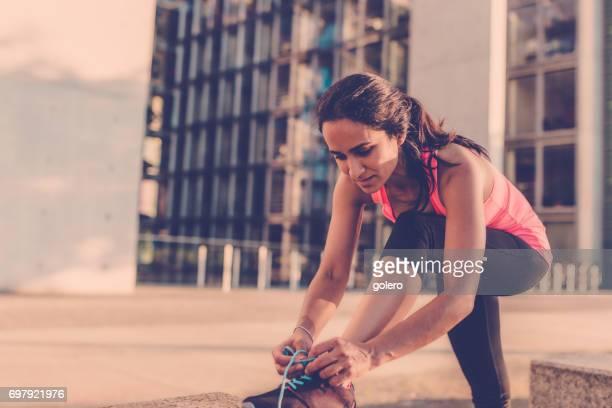 brazilian sportswoman tying shoe in city