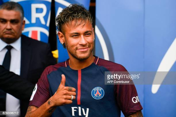 Brazilian superstar Neymar gestures as he arrives to greet supporters during his official presentation at the Parc des Princes stadium on August 4...