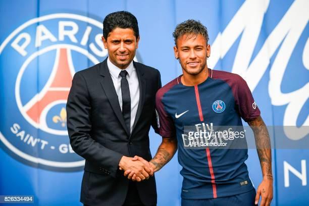 TOPSHOT Brazilian superstar Neymar shakes hands with Paris Saint Germain's Qatari president Nasser AlKhelaifi during a press conference at the Parc...