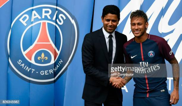 Brazilian superstar Neymar shakes hands with Paris Saint Germain's Qatari president Nasser AlKhelaifi during a press conference at the Parc des...