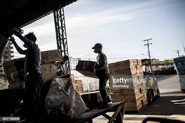 Brazilian Tax Authority workers put packages of Eight brand cigarettes into a shredder after they were seized from smugglers near the border with...