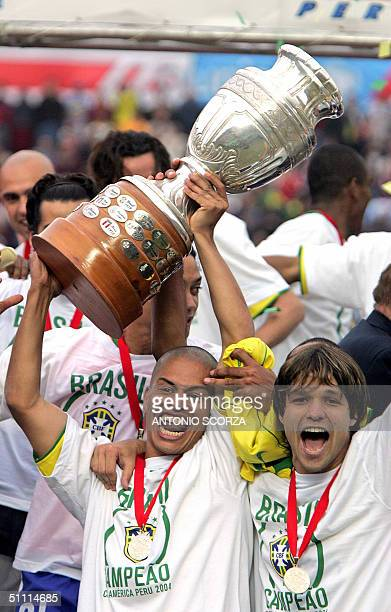 Brazilian team captain Alex de Souza holds the Copa America 2004 trophy 23 July 2004 beside his teammate Diego da Cunha after defeated Argentina by...