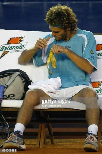 Brazilian tennis player finishes a snack during his match against Spain's David Ferrer 26 February 2003 El brasileno Gustavo Kuerten termina de comer...