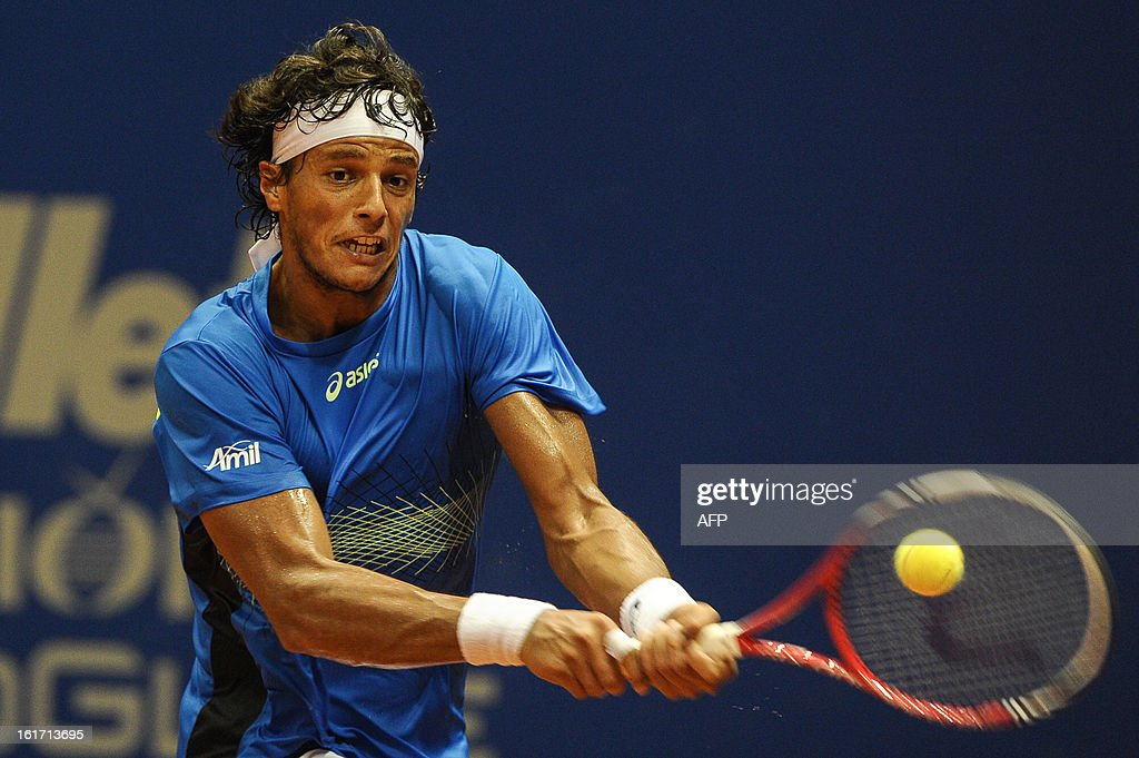 Brazilian tennis player Joao Souza hits a return against Spanish Rafael Nadal during a Brazil Open single match at Ibirapuera gymnasium in Sao Paulo, Brazil, on February 14, 2013. Nadal withdrew his doubles match yesterday because of his left knee concern. AFP PHOTO/Yasuyoshi CHIBA